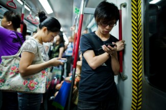 People using smartphones in subway train